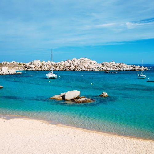 Cala Acciarino, la plus belle plage des îles Lavezzi en Corse avec un catamaran à l'ancre
