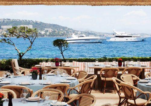 Des tables sont installées pour le déjeuner sur la terrasse de La Guérite à Cannes avec des yachts au mouillage