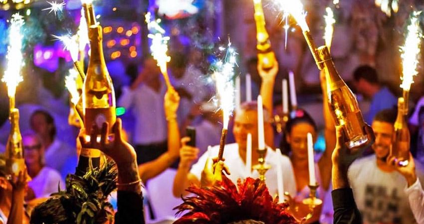 Bouteilles de champagne avec des scintillants et des gens qui dansent lors d'une soirée à L'Opéra à Saint-Tropez