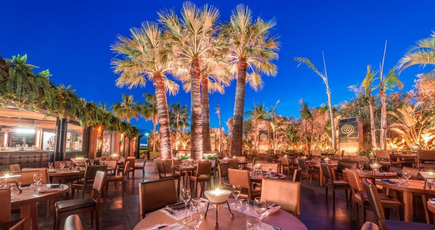 La terrasse du Baoli à Cannes à la tombée de la nuit avec des éclairages dans les palmiers