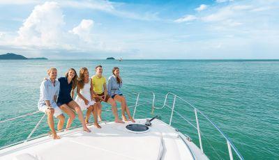 Des jeunes gens souriant à l'avant d'un yacht à moteur disponible à la location pour les groupes