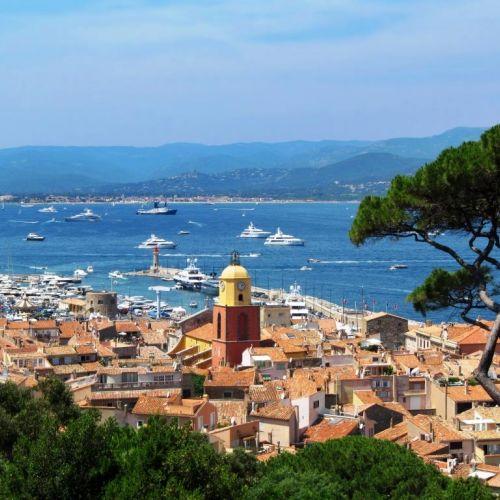 Vue du village de Saint-Tropez avec son clocher et des yachts de location à l'ancre dans la baie