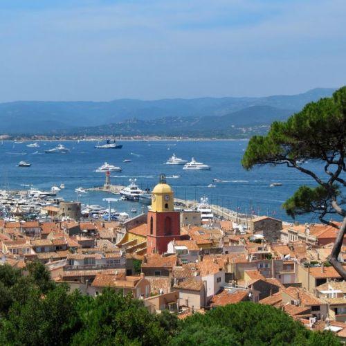 Le village de Saint-Tropez et son clocher avec des yachts à l'ancre dans la baie