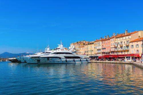Le port de Saint-Tropez avec le Café Sénéquier et des yachts de location amarrés