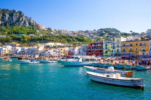 Le petit port de Capri avec ses bateaux et ses maisons colorées sous un beau ciel bleu