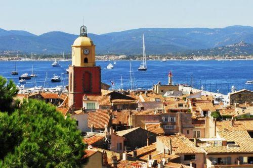 Panorama du village de Saint-Tropez avec son clocher et des yachts à l'ancre dans la baie