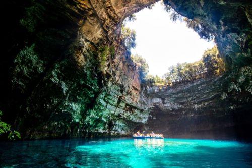 Des gens sur un bateau explorant l'impressionnante Melissani Cave sur l'île de Céphalonie en Grèce
