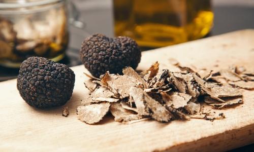 Deux truffes blanches et des copeaux sur une planche en bois d'olivier