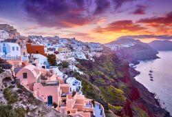Le village d'Oia sur l'île de Santorin avec un superbe coucher de soleil et des reflets rose sur les maisons