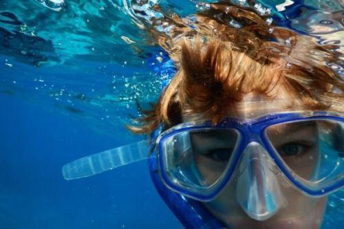 Un garçon faisant du snorkeling avec masque et tuba
