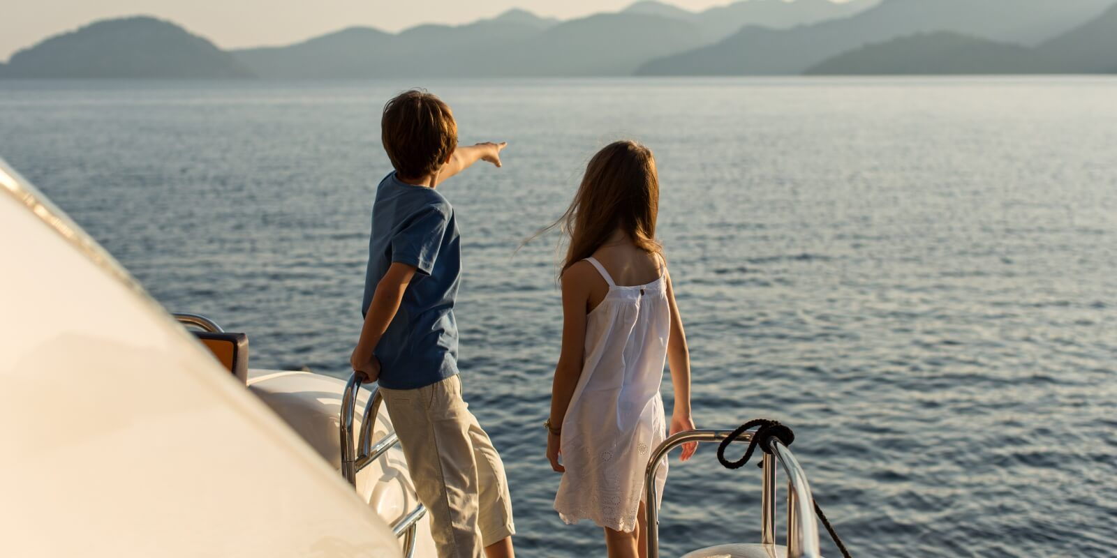 https://www.talamare.fr/medias/Des enfants regardant la mer depuis un yacht de location avec leurs parents sur le pont arrière