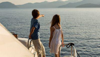 Des enfants regardant la mer depuis un yacht de location avec leurs parents sur le pont arrière