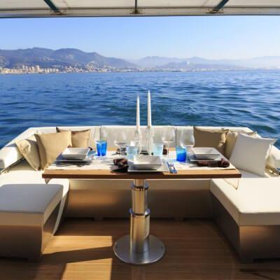 Une table dressée pour le déjeuner sur le pont arrière d'un yacht de location de luxe disponible sur la Côte d'Azur